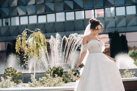 Portrait of the bride in the city near the fountain.A stunning young bride with curly hair . Wedding day. . Beautiful portrait of the bride without the groom Stock fotó