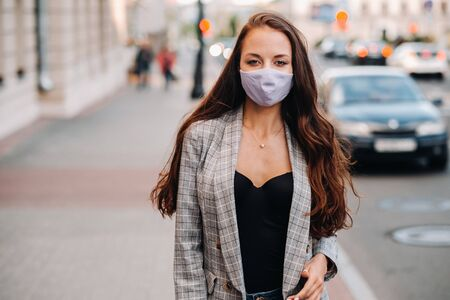 Covid-19 and Air pollution pm2.5 concept. Pandemic, portrait of a young woman wearing protective mask on street. Concept health and safety.