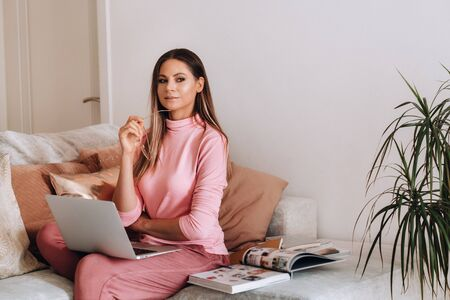 a girl in the morning in pajamas and glasses at home works on a laptop, a girl self-isolates at home and rests on the couch and watches a laptop.Household chores.