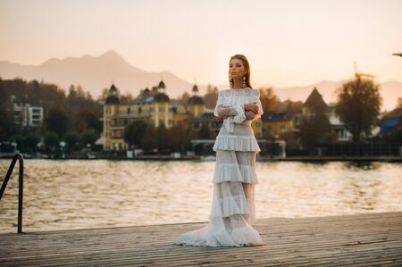 Bride in white wedding dress in the old town of Velden am w rthersee.Model in a wedding dress in Austria.Alps. 免版税图像 - 150154592