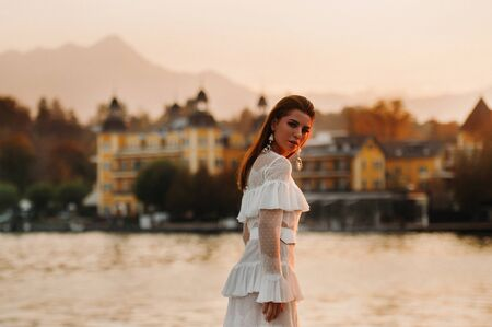 Bride in white wedding dress in the old town of Velden am w rthersee.Model in a wedding dress in Austria.Alps. 免版税图像 - 150154613