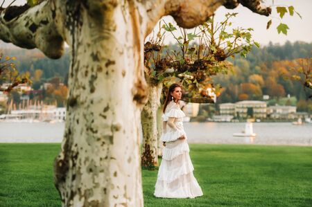 A bride in a white wedding dress with a belt in the Old town of Velden am werter see.A model in an Austrian wedding dress.Alps. 免版税图像 - 150154633