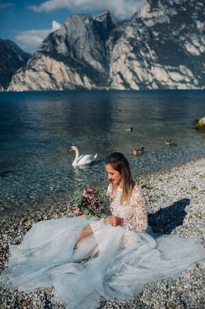 a girl in a smart white dress is sitting on the embankment of lake Garda.A woman is photographed against the background of a mountain and lake in Italy.Torbole.