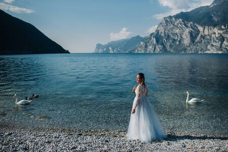 a girl in a smart white dress walks along the embankment of lake Garda.A woman is photographed against the background of a mountain and lake in Italy.Torbole.
