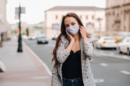 Covid-19 and Air pollution pm2.5 concept. Pandemic, portrait of a young woman wearing protective mask on street. Concept health and safety