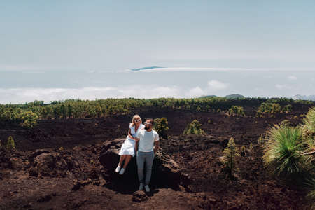 The family in white clothes are tourists traveling through the summer mountains of the Teide volcano in Tenerife. A young couple on a rocky mountain range looks at a beautiful view in the clouds and at the island of Gomera, Canary Islands. 写真素材