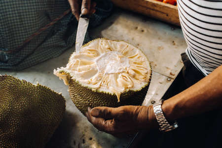 The seller cuts a juicy, ripe jackfruit for tourists. The urban market of Port Louis, Mauritius. Stock Photo