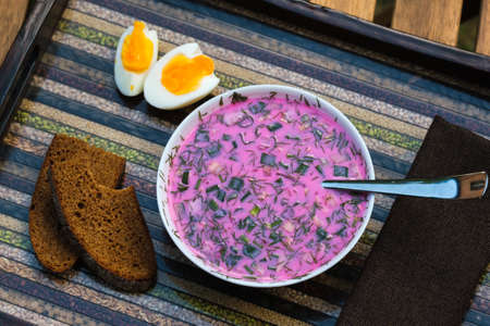 Cold beetroot soup with eggs and bread on a decorative tray.Soup kholodnik red on an unusual tray. Food. Reklamní fotografie