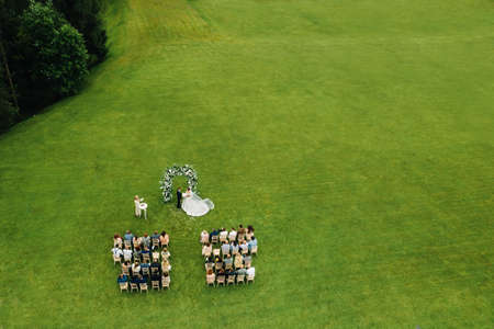 Top view of the Wedding ceremony in a green field with guests sitting on chairs. Wedding venue on the green lawn Archivio Fotografico