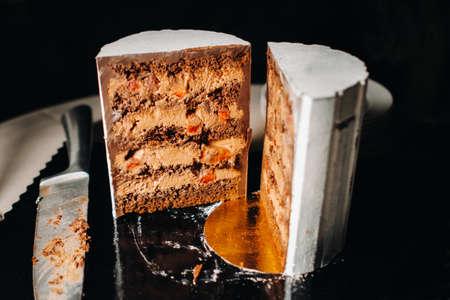 Amazing Cakes. Sliced chocolate wedding cake cake with amazing filling on a black background.Large cake in white chocolate.