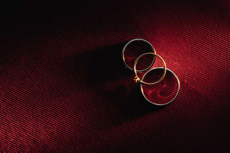 Two wedding rings and one engagement ring on a red background. three Gold rings of a couple in love.Concept of love.Wedding ring.