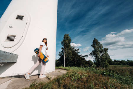 A girl in white clothes and glasses with a skate in her hands is photographed near large wind turbines in a field with trees.Modern woman with a riding Board in a field with windmills. 版權商用圖片