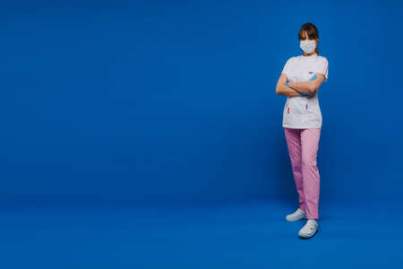 A girl doctor stands in a medical mask, isolated on a blue background