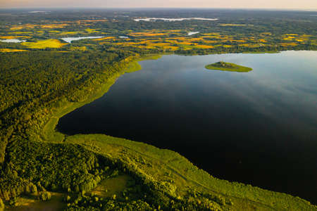 Top view of lake Drivyaty in the forest in the Braslav lakes National Park at sunset, the most beautiful places in the city of Belarus.An island in the lake.Belarus.
