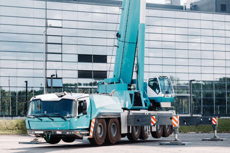 A large blue truck crane stands ready to operate on hydraulic supports on a platform next to a large modern building. The largest truck crane for solving complex tasks.