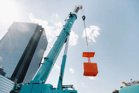 A large blue truck crane stands ready for operation on a site near a large modern building. The largest truck crane with a yellow cradle for solving complex tasks