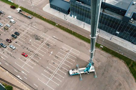 view from the height of the Car heavy crane that stands open in the Parking lot and ready to work. the highest truck crane is deployed on the site. the height of the boom is 80 meters 版權商用圖片