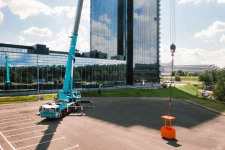 view from the height of the car of a heavy crane with a cradle, which is open in the Parking lot and ready to work. the highest truck crane is deployed on the site. the height of the boom is 80 meters