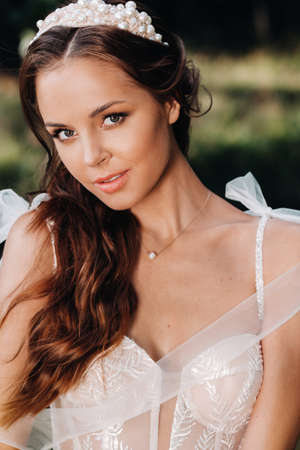 Close-up portrait of an Elegant bride in a white dress in nature in a nature Park.Model in a wedding dress and gloves .Belarus