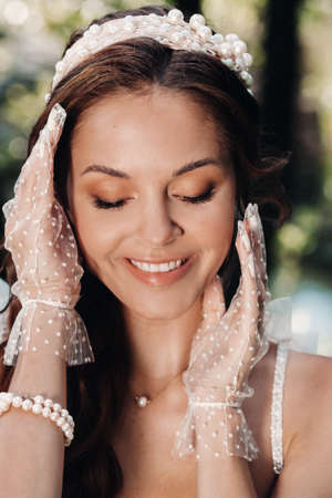 An elegant bride in a white dress, gloves with a bouquet on a waterfall in the Park, enjoying nature.Model in a wedding dress and gloves in the forest.Belarus 版權商用圖片