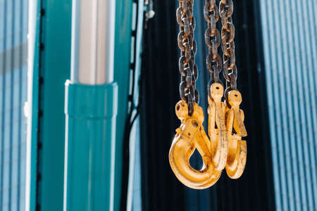 The hooks of the mobile crane near the glass of high buildings.Lots of hooks hanging from chains suspended from a crane