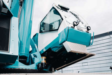a cab with the operator of a Large blue car crane that stands ready to operate on hydraulic supports on a platform next to a large modern building. The largest truck crane for solving complex tasks.
