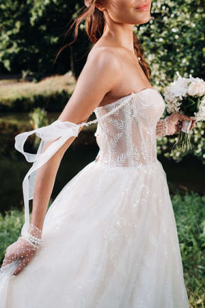 portrait of an elegant bride in a white dress with a bouquet in nature in a nature Park.Model in a wedding dress and gloves and with a bouquet .Belarus 版權商用圖片