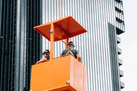 Workers in a construction cradle climb on a crane to a large glass building.The crane lifts the workers in the car seat.Construction