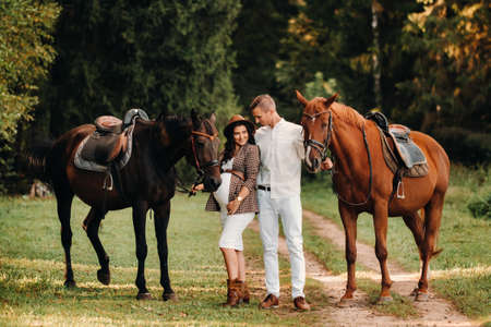 a pregnant girl in a hat and her husband in white clothes stand next to horses in the forest in nature.Stylish pregnant woman with a man with horses.Family. Imagens