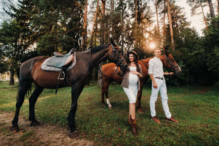 a pregnant girl in a hat and her husband in white clothes stand next to horses in the forest in nature.Stylish pregnant woman with a man with horses.Family. Archivio Fotografico