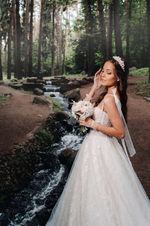 An elegant bride in a white dress and gloves holding a bouquet stands by a stream in the forest, enjoying nature.A model in a wedding dress and gloves in a nature Park.Belarus