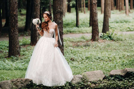 An elegant bride in a white dress and gloves holding a bouquet stands by a stream in the forest, enjoying nature.A model in a wedding dress and gloves in a nature Park.Belarus.