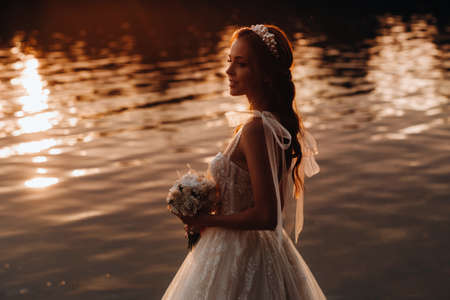 An elegant bride in a white dress and gloves stands by the river in the Park with a bouquet, enjoying nature at sunset.A model in a wedding dress and gloves in a nature Park.