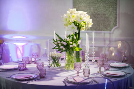 decoration of a festive dinner with flowers of lilies and tulips on the wedding table in the interior of the restaurant. Decorated table for a celebration in purple tones. Foto de archivo