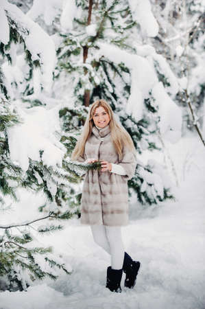 Portrait of a woman in a white fur coat in a cold winter forest. Girl in a snow-covered winter forest.