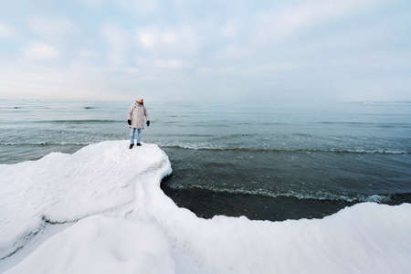 A tourist stands on the shore of the Baltic sea in winter. Winter near the Baltic States of Tallinn.Traveler near the sea in winter. Stok Fotoğraf