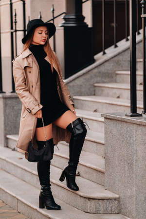 Stylish young woman in a beige coat in a black hat on a city street. Women's street fashion. Autumn clothing.Urban style. Stockfoto