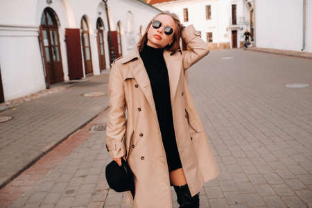 Stylish young woman in a beige coat and a black hat in his hands and glasses on a city street. Women's street fashion. Autumn clothing.Urban style Foto de archivo