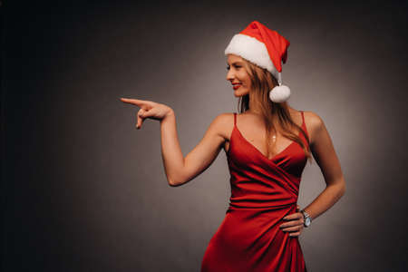 a woman in a red dress and a Christmas hat points her fingers at a black background.Smiling girl in new year shows direction on dark background.