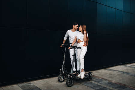 A girl and a guy are walking on electric scooters around the city, a couple in love on scooters.