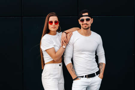 A beautiful couple in love in white stylish clothes are walking in the city Reklamní fotografie