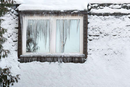 Icicles on the window of the house on a frosty day..