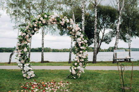 Wedding ceremony on the street on the green lawn.Decor with fresh flowers arches for the ceremony.
