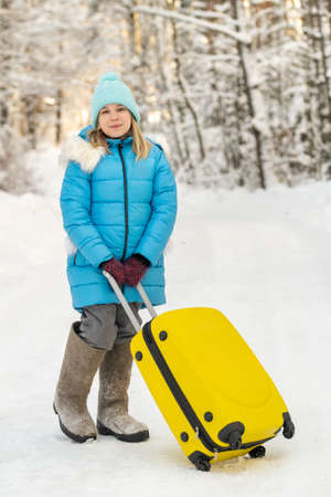 A girl in winter in felt boots goes with a suitcase on a frosty snowy day Stock Photo