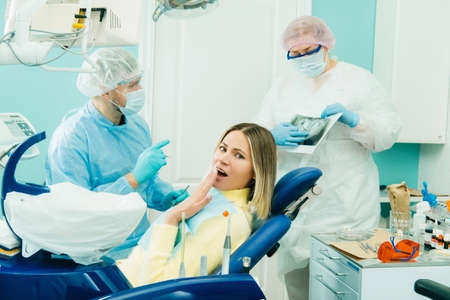The dentist explains the details of the X-ray to his colleague, the patient is surprised by what is happening.