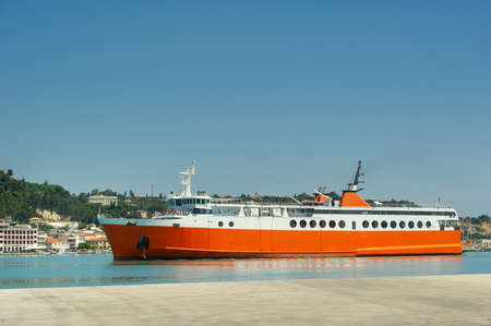 Large red ferry for transporting cargo and people in the Mediterranean Sea near the Greek island promenade, Greece.