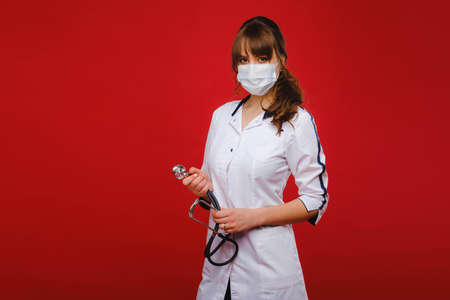 A young doctor in a white coat and medical mask stands on a red background.