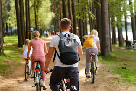 A group of cyclists with backpacks ride bicycles on a forest road enjoying nature.