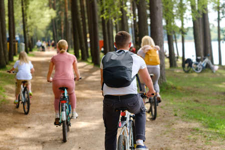 A group of cyclists with backpacks ride bicycles on a forest road enjoying nature. Standard-Bild