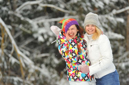 Two girls in the winter forest emotionally hug and smile.Happy women hug and Express joy Reklamní fotografie